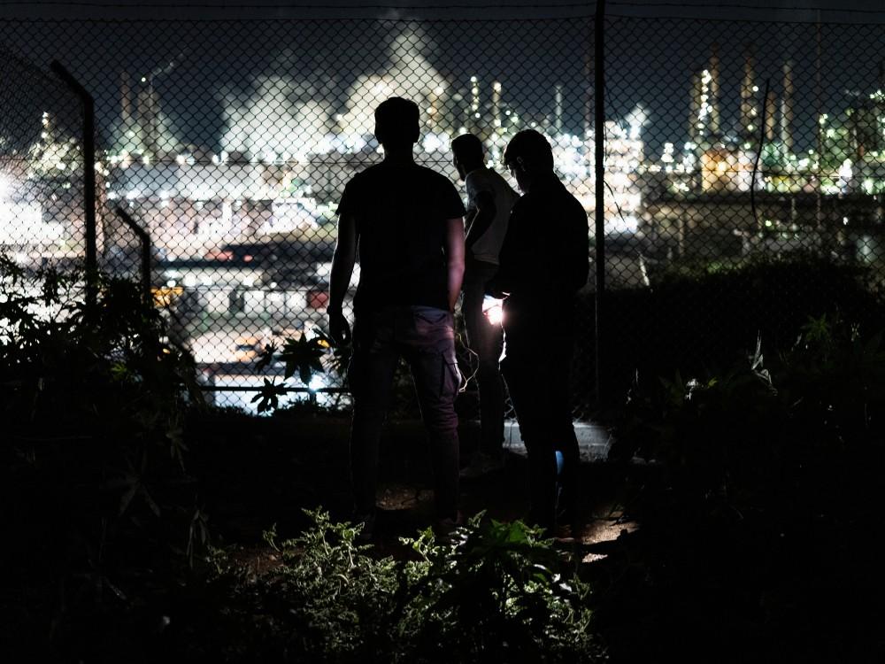 Die Jugendlichen Adrian, Mido und Enzo schauen durch den Zaun einer  Ölraffinerie von Sonatrach, Priolo Gargallo, 2019