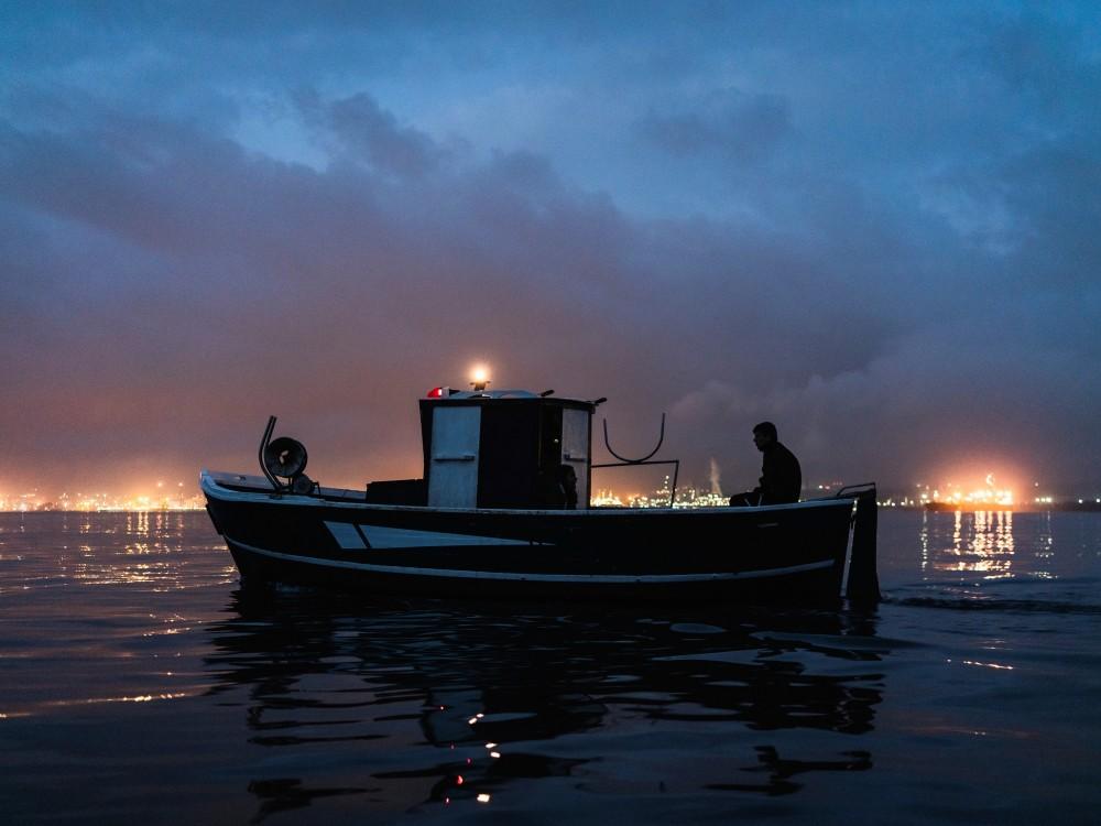 Ein Fischer fährt zu seinem Netz, während am Horizont die Raffinerien leuchten, Augusta, 2019